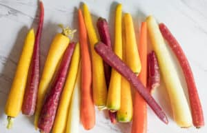 three color carrots in a row ready for roasting