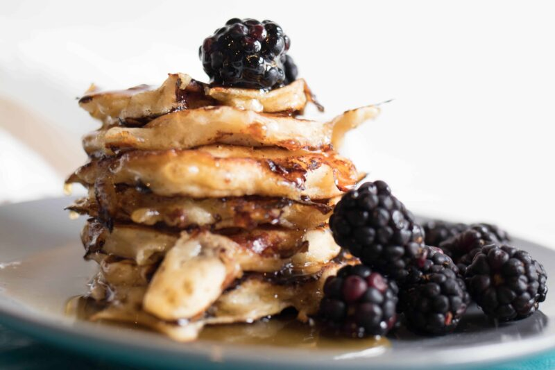 cottage cheese pancakes on a plate with syrup and blackberries