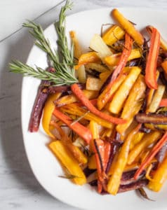 roasted carrots with rosemary sprig on a white plate
