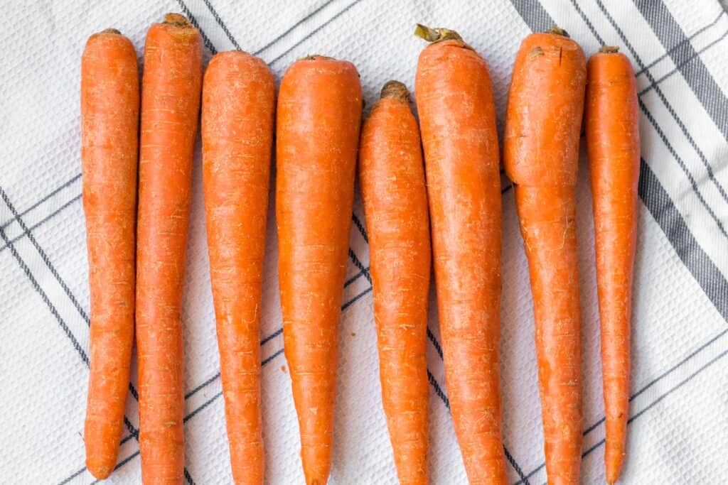 carrots of different sizeds lined up on a kitchen towel