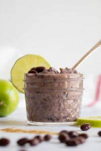 Pureed black beans in a small glass jar.  Whole black beans and lime slices on the table.