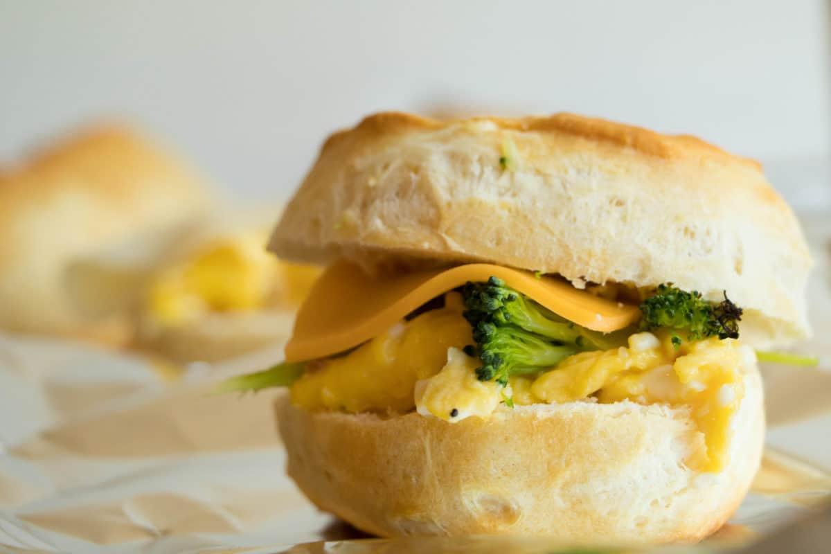 breakfast sandwich on a biscuit with scrambled eggs, broccoli and cheddar cheese