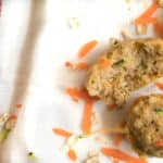 carrot zucchini muffin on dish towel with carrot shreds