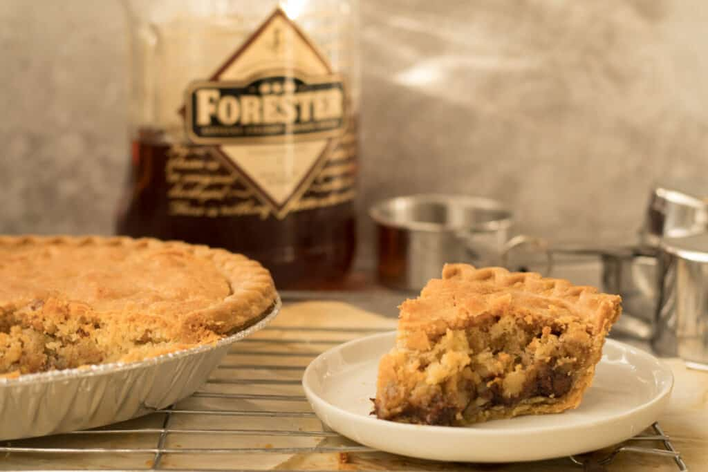 piece of derby pie with bottle of old forrestor in the background