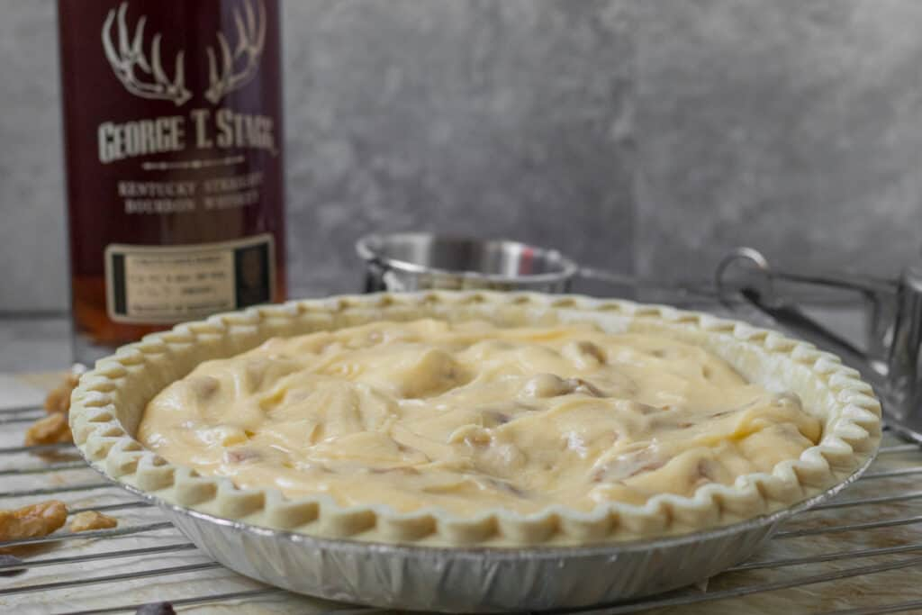 derby pie ready for baking with bottle of bourbon behind it