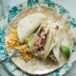 three fish tacos on a plate with corn and lime wedges