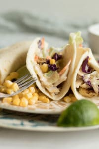 three fish tacos with spicy slaw on a plate with a fork, corn and lime wedge