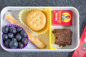 cheese stick, crackers, raisins, blueberries and brownie in a lunch box