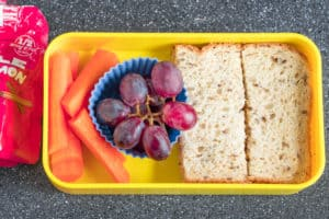 yellow container with lunch idea of carrots, grapes and peanut butter and jelly sandwich.