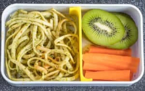 pesto pasta with kiwi slices and carrot sticks in a lunch box