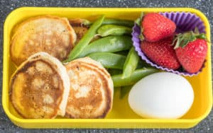 pancakes, snap peas, strawberries, hard boiled eggs in a lunch box