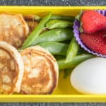 pancakes, sugar snap peas, strawberries and hard boiled egg in lunchbox