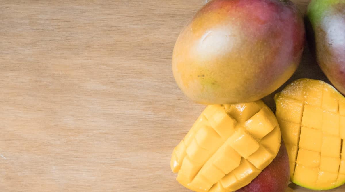 whole mango and cut mango on a wooden board