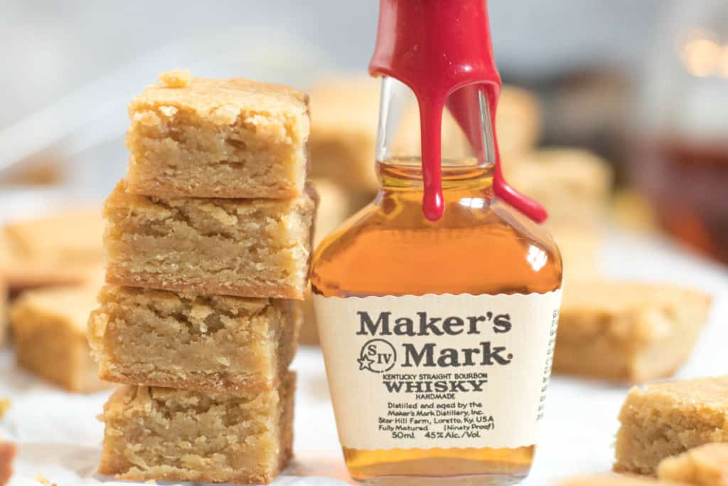 stack of four blondies next to a small bottle of makers mark bourbon