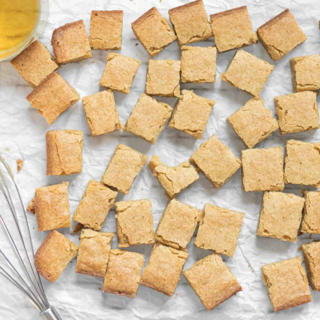 lots of little bourbon blondies scattererd on parchment paper with a glass of bourbon and a whisk