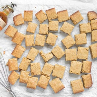 batch of boozy bourbon blondies scattered on parchment paper with a small bottle of blantons bourbon and a whisk