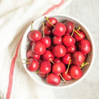 bowl of red cherries next to a white towel with a red stripe