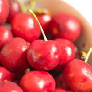 a bowl of cherries with one perfect red cherry in focus on top.