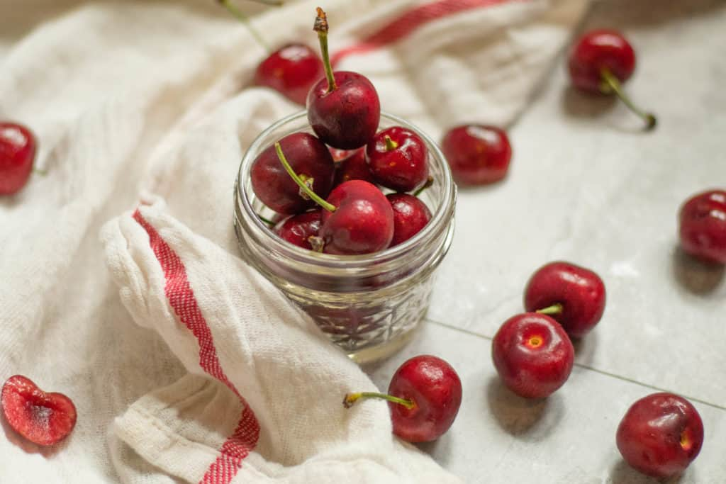 cherries piled in a small mason jar with other cherries scattered about on a towel.