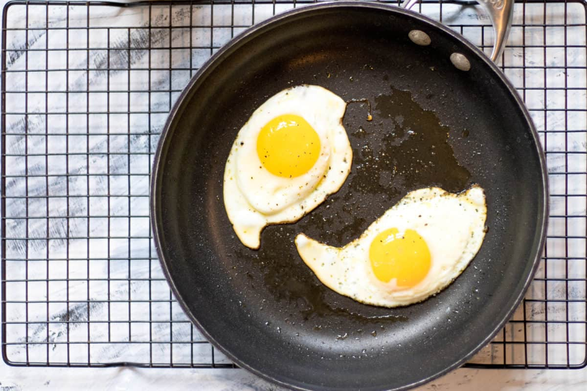 two over easy eggs in a black frying pan on a cooling rack
