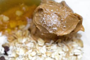 dollop of peanut butter on a bed of oats and honey in a glass bowl.