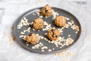 5 energy bites on a gray plate surrounded by raw oats