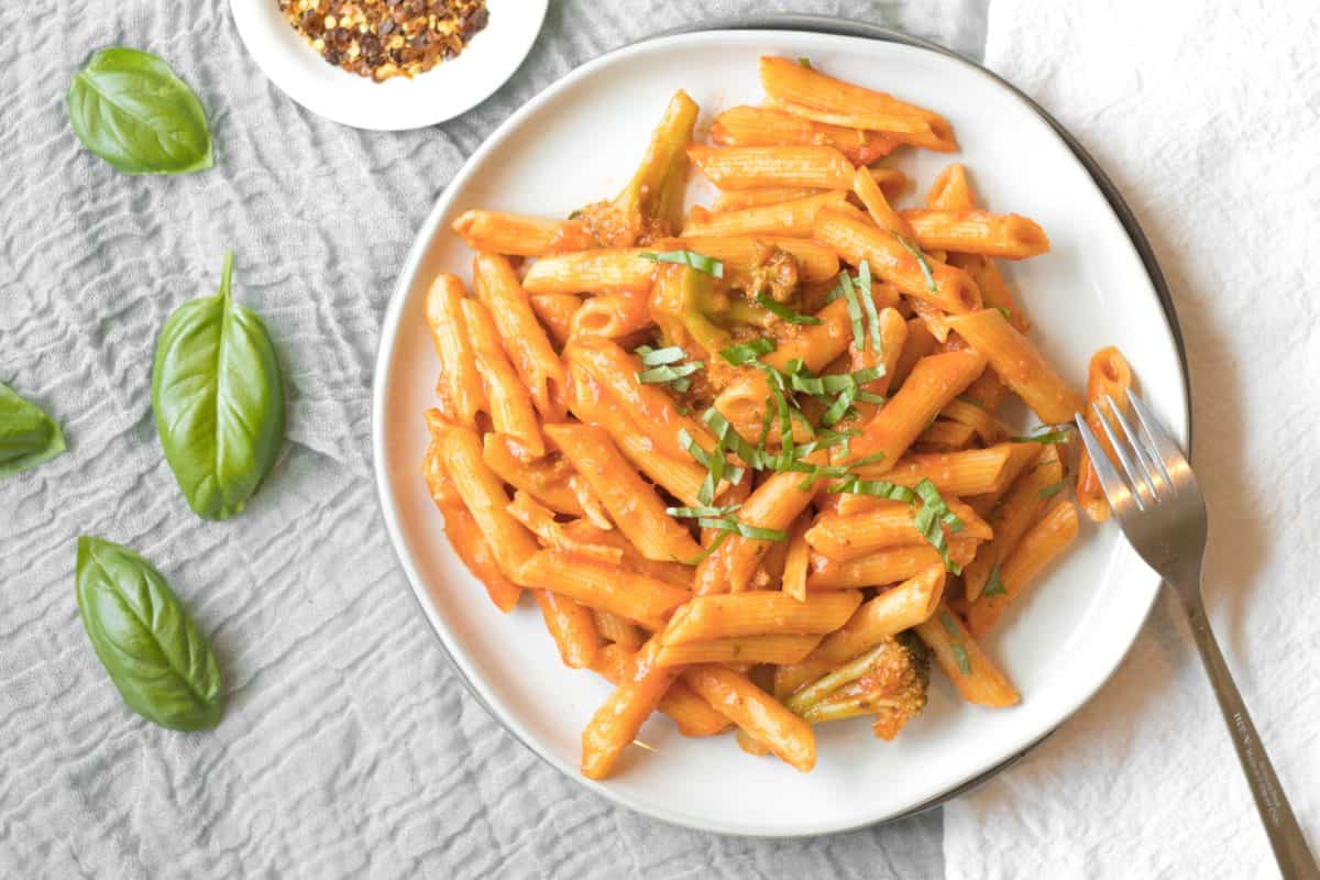 white plate of penne pasta with a red sauce and basil garnish. a small plate of red pepper flakes is in the background with whole basil leaves