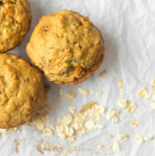 three apple cinnamon oatmeal breakfast muffins on parchment paper with rolled oats