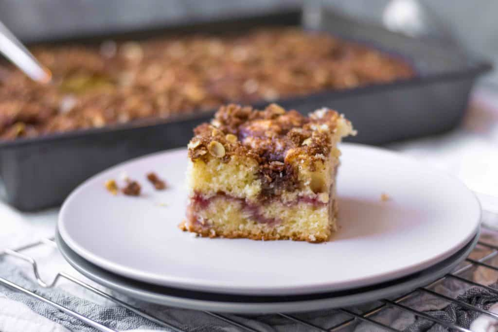 piece of coffee cake with strawberry jam middle on a double stacked plate with pan of cake in the background