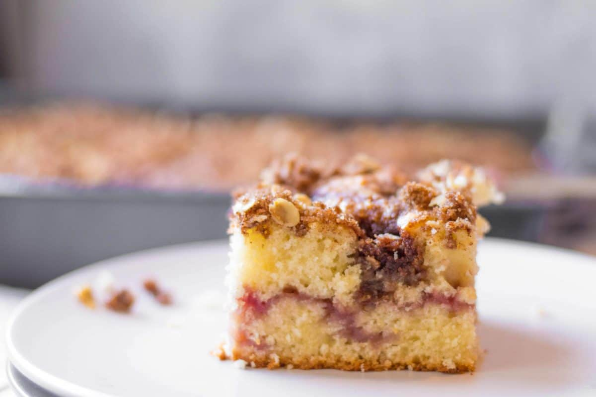 coffee cake with struesel on top and a strawberry jam swirl in the middle with a full pan of coffee cake out of focus in the background