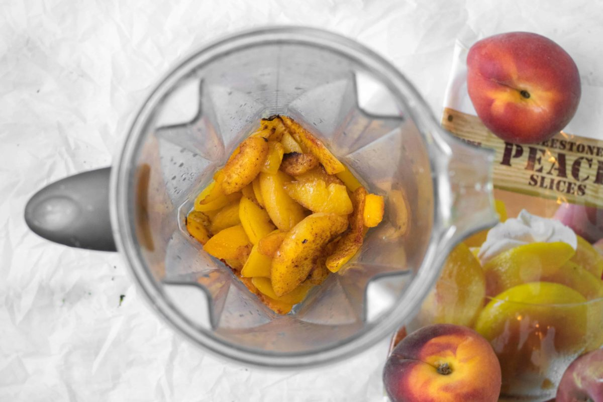 sliced peaches in a vitamix blender with frozen and fresh peaches surrounding