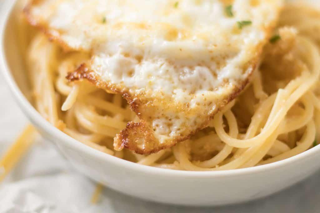 up close crispy edge of a fried egg over pasta pangrattato