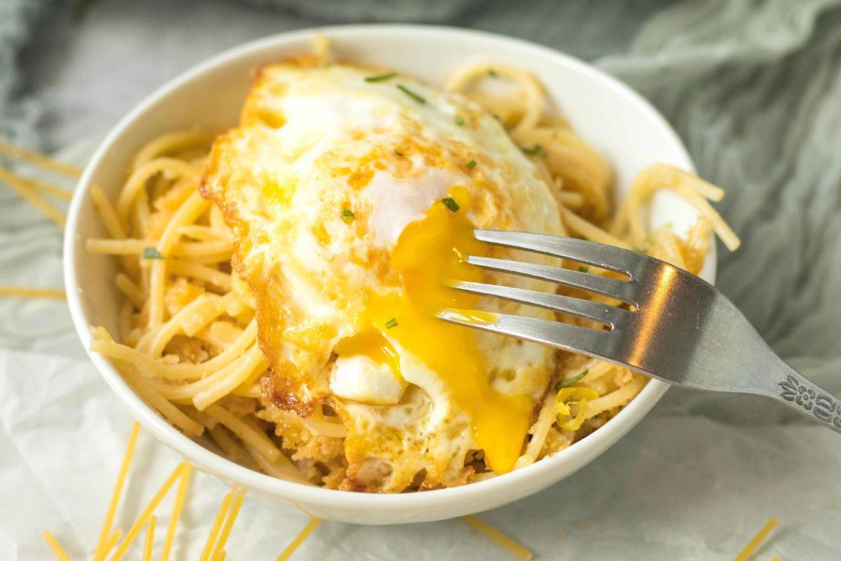 oozing egg yolk of a fried egg over pasta pangrattato