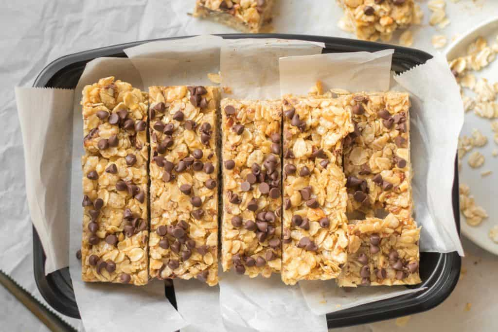 simple granola bars with chocolate chips packed in a tupperware with parchment paper
