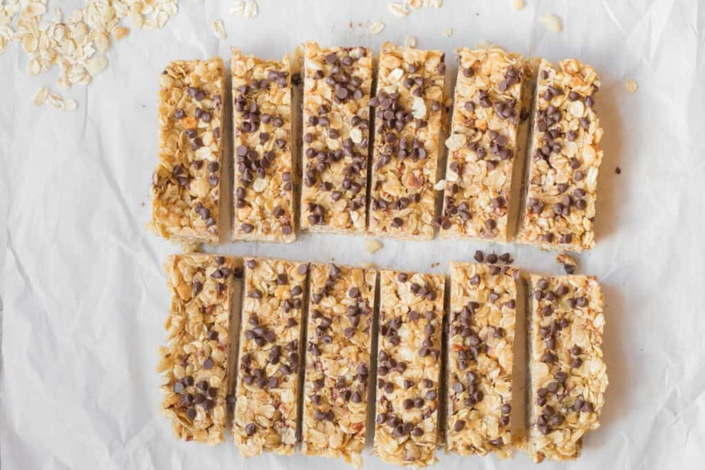 twelve simple granola bars with chocolate chips on parchment paper