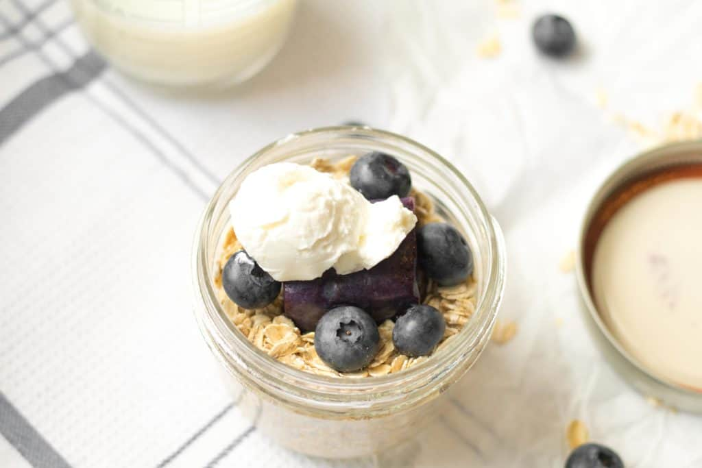overnight oats, blueberries and greek yogurt in an 8 oz mason jar with lid next to it on table