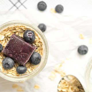 oats in a mason jar with a cube of frozen blueberry puree and fresh blueberries