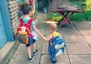 two kids with backpacks getting ready to go back to school