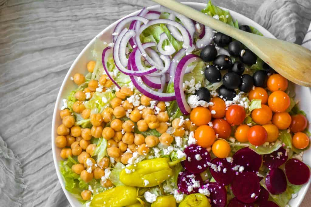 composed greek salad with piles of chickpeas, onions, tomatoes olives, beets and pepperoncinis on big serving dish with wooden spoon