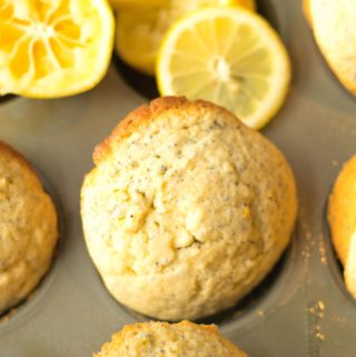 lemon poppy seed muffins in a muffin tin with squeezed lemons behind them