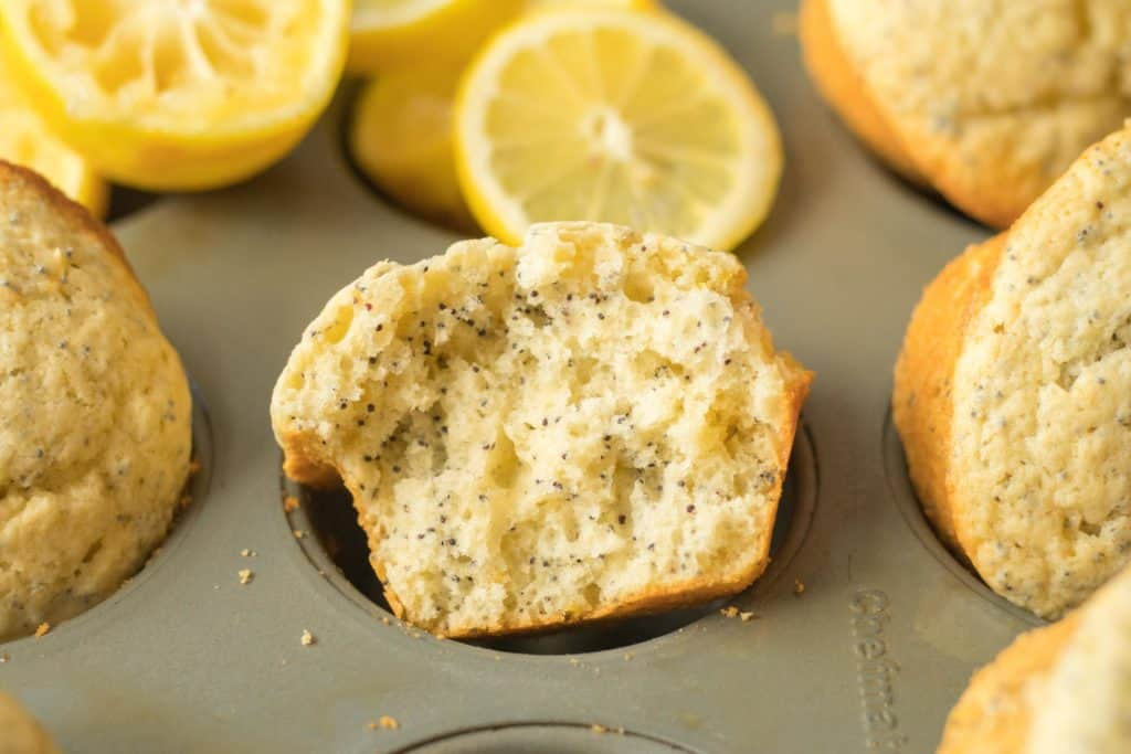 half a lemon poppy seed muffin in a muffin tin with sliced lemon