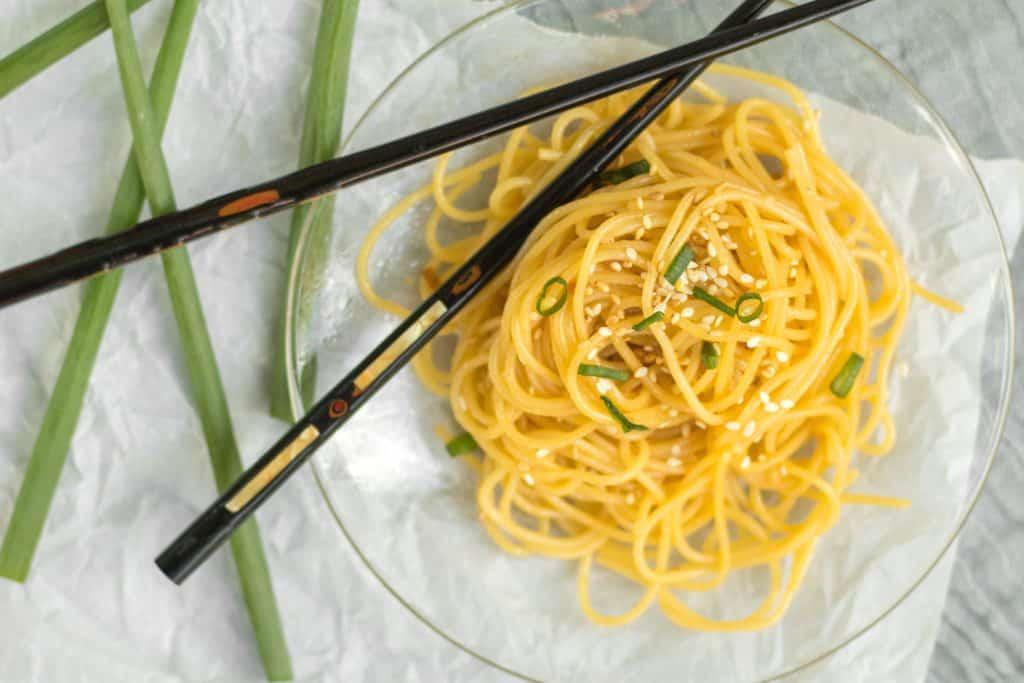 sesame noodles on glass plate with black chopsticks