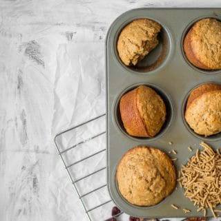 all bran muffins in a muffin tin with one filled with cereal on a cooling rack