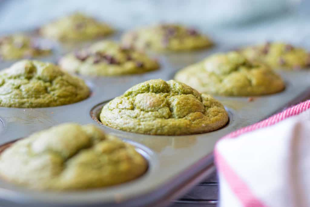 side view of green blender muffins in a muffin tin