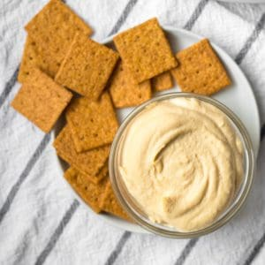 homemade hummus in a small glass dish with wheat crackers on a plate