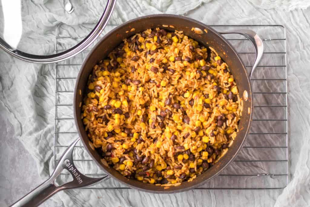 mexican rice skillet in a pan on a cooling rack with lid