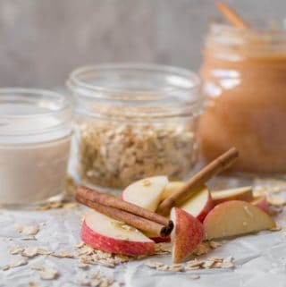 jars of milk, oats and applesauce behind a pile of sliced apples