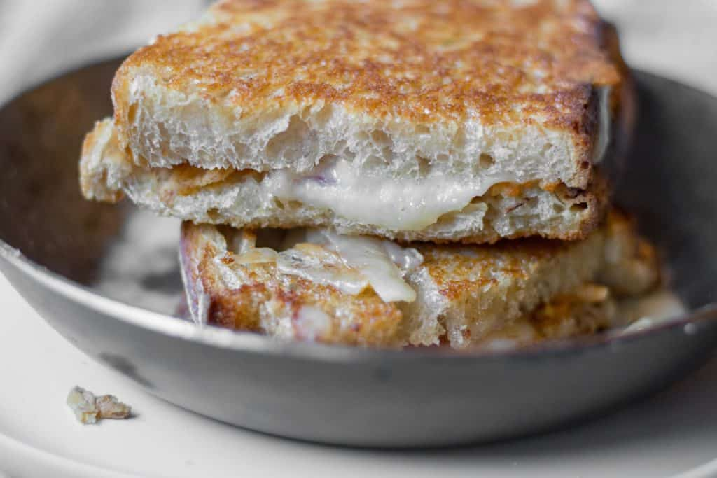side view of a grilled cheese sandwich with melty cheese dripping down