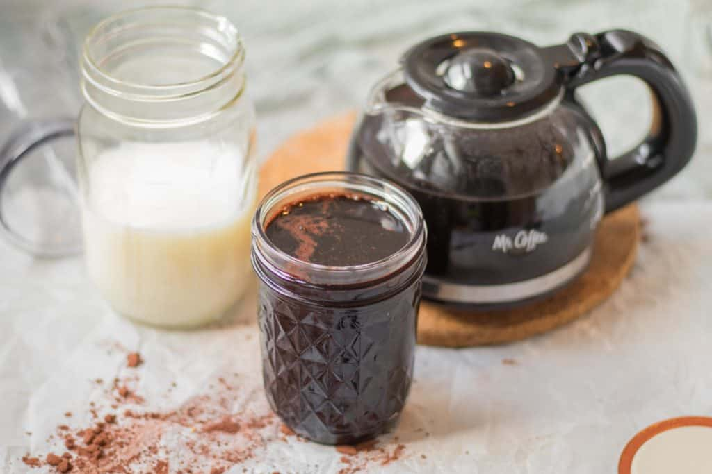 ingredients needed for iced coffee, black coffee, milk and homemade chocolate syrup