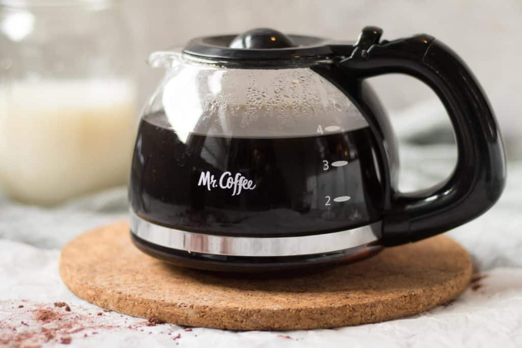 4 cup mr. coffee pot with black coffee on a trivet